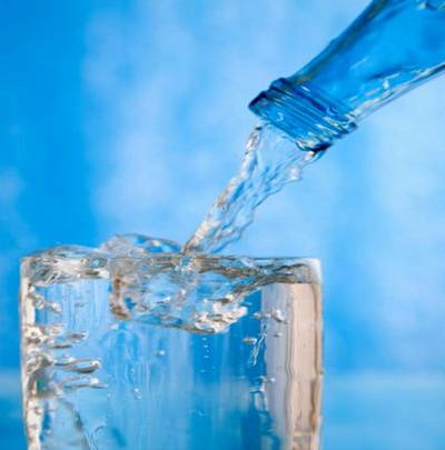 Glass of water with ice on a blue background